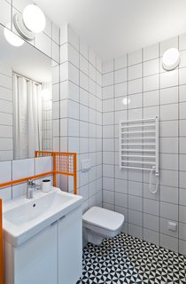 The bathroom features graphic eye-catching Vives floor tiles surrounded by Opoczno wall tiles and clean white plumbing fixtures. The custom-designed orange sink frame adds a whimsical pop of color.