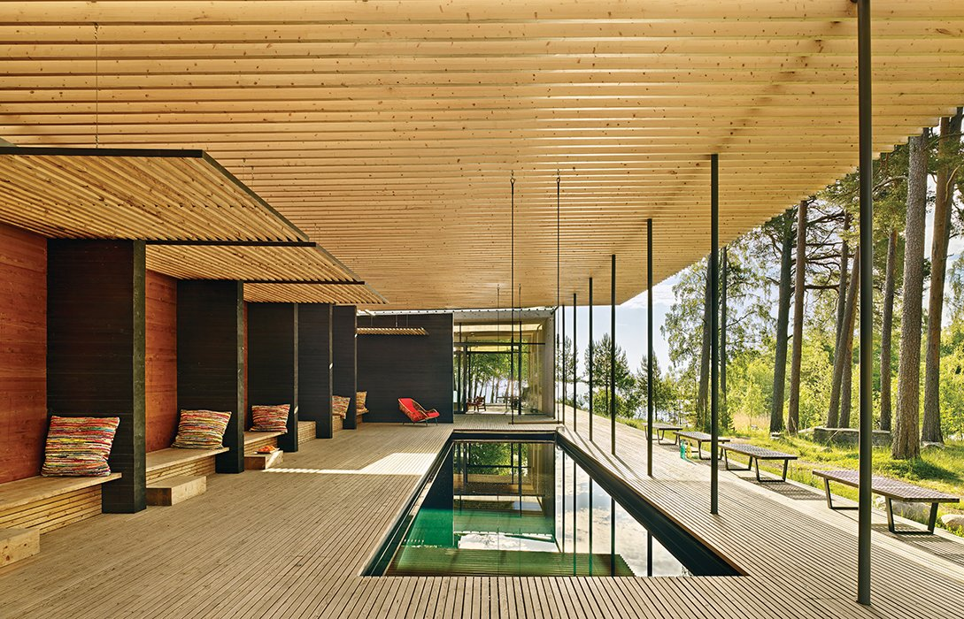 In Sweden, architect Bengt Mattias Carlsson created a pavilion adjacent to a residence dating from the late 1800s. The pergola is made from glue-laminated timber beams set atop steel posts; it protects the pool from falling pine needles. George Nelson benches offer places to sit. Tagged: Outdoor, Large Patio, Porch, Deck, Decking Patio, Porch, Deck, Trees, Grass, Plunge Pools, Tubs, Shower, and Wood Patio, Porch, Deck.  Photo 1 of 8 in How a 1,000-Year-Old Technique Made This Pavilion