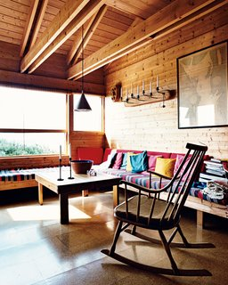 Built-in benches function both as seating and as spare beds in the living room. Holm says the striped, hand-woven fabric she found in Greece is indestructible, and the cork flooring throughout the house has gone 40 years without needing replacing.