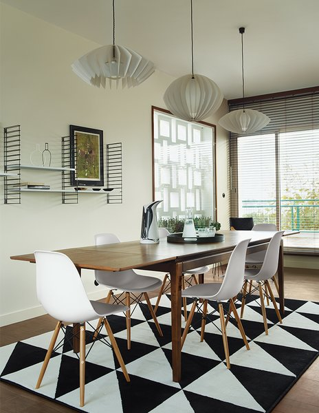 The dining table is from French retailer AM.PM., the pendants are by Him + Her, and the shelves are by Tomado Holland. An Ikea rug echoes the geometric motif found throughout the apartment.