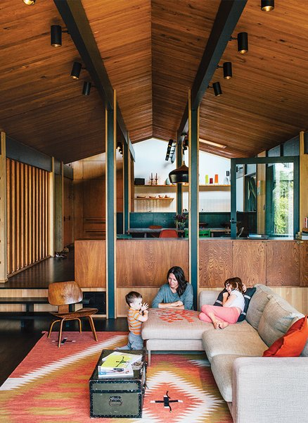The living room sports a panoply of wood: Douglas fir for the ceiling, hemlock for the walls, and stained oak for the floor. The sofa is the Neo model by Bensen and the rug is vintage.