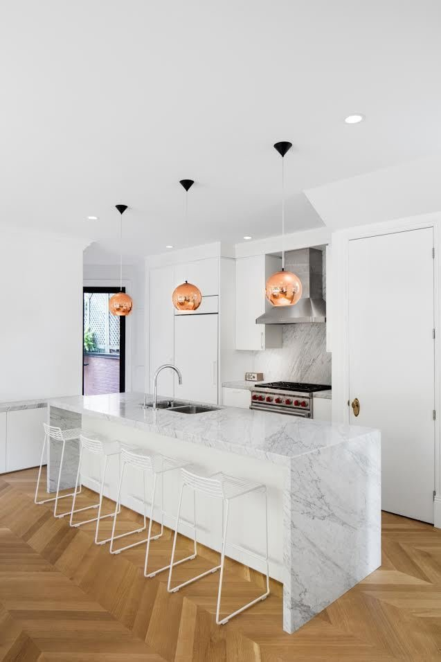 """Kitchen, Range Hood, Marble Counter, Pendant Lighting, Range, White Cabinet, Undermount Sink, Medium Hardwood Floor, Marble Backsplashe, and Recessed Lighting """"We placed the kitchen at the center of the house to link with the dining room and the outdoor space,"""" Moreau says. In the kitchen, a Wolf oven brings out the silver details in Coit's Bianco Cararra backsplash and island. Hee bar stools by Hay are lined under the island.  Photo 20 of 21 in Mad About Marble: 20 Kitchens and Bathrooms from This House Looks Great After 107 Years"""