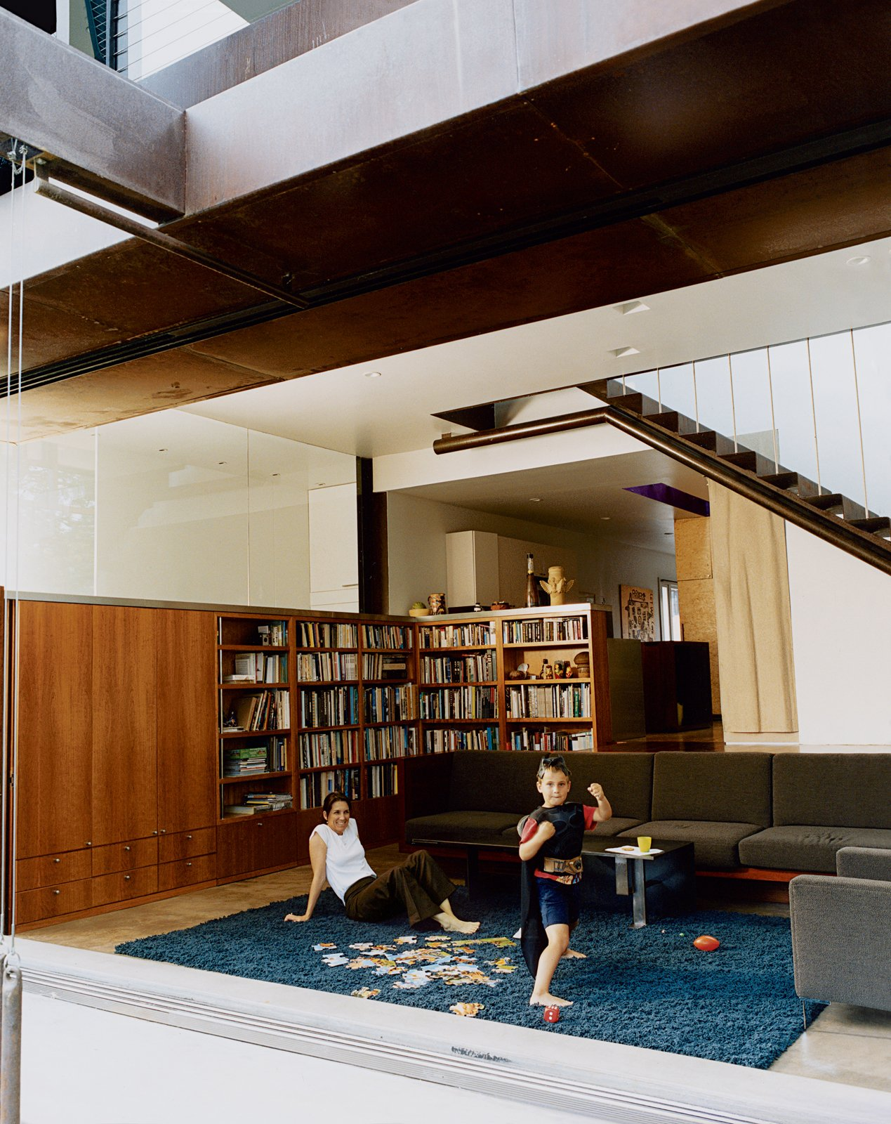 Living Room Angela Brooks and son Calder revel in the benefits of free solar energy, cheerfully opening the living room's big glass doors when it's time to play.  Photo 2 of 8 in Solar Inspiration