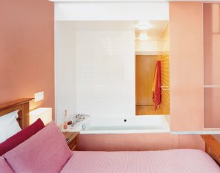 "In a major renovation and addition to an existing row house in Harlem, Laura Briggs and Jonathan Knowles designed unusual adjacencies, including this hot tub that opens into the master bedroom with sliding panels. The pink bed linens flow into the burnt orange-pink of the walls, which transitions into the orange bathroom beyond. <span style=""color: rgb(204, 204, 204); font-size: 13px;"">Photo by Adam Friedberg</span>"