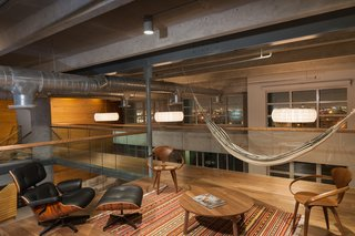A Miami Renovation That Blends Concrete and Rich Wooden Interiors - Photo 5 of 7 - A classic piece like this Eames lounge chair appears dressed down next to a hammock in the office space. Also featured are wooden office chairs by Norman Cherner.