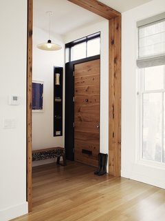 Even a few pieces of salvaged lumber can have a big impact. This entryway in a Brooklyn townhouse, renovated by Bangia Agostinho Architecture, reused hemlock fir joists from the existing building structure as casework around the main entry door. The trim has a simple, modern profile, ensuring that it makes a contemporary statement. In the entryway is another repurposed piece of wood that was charred in a fire more than 100 years ago. It has since been painted and repainted—creating a unique patina and texture—and transformed into a bench.