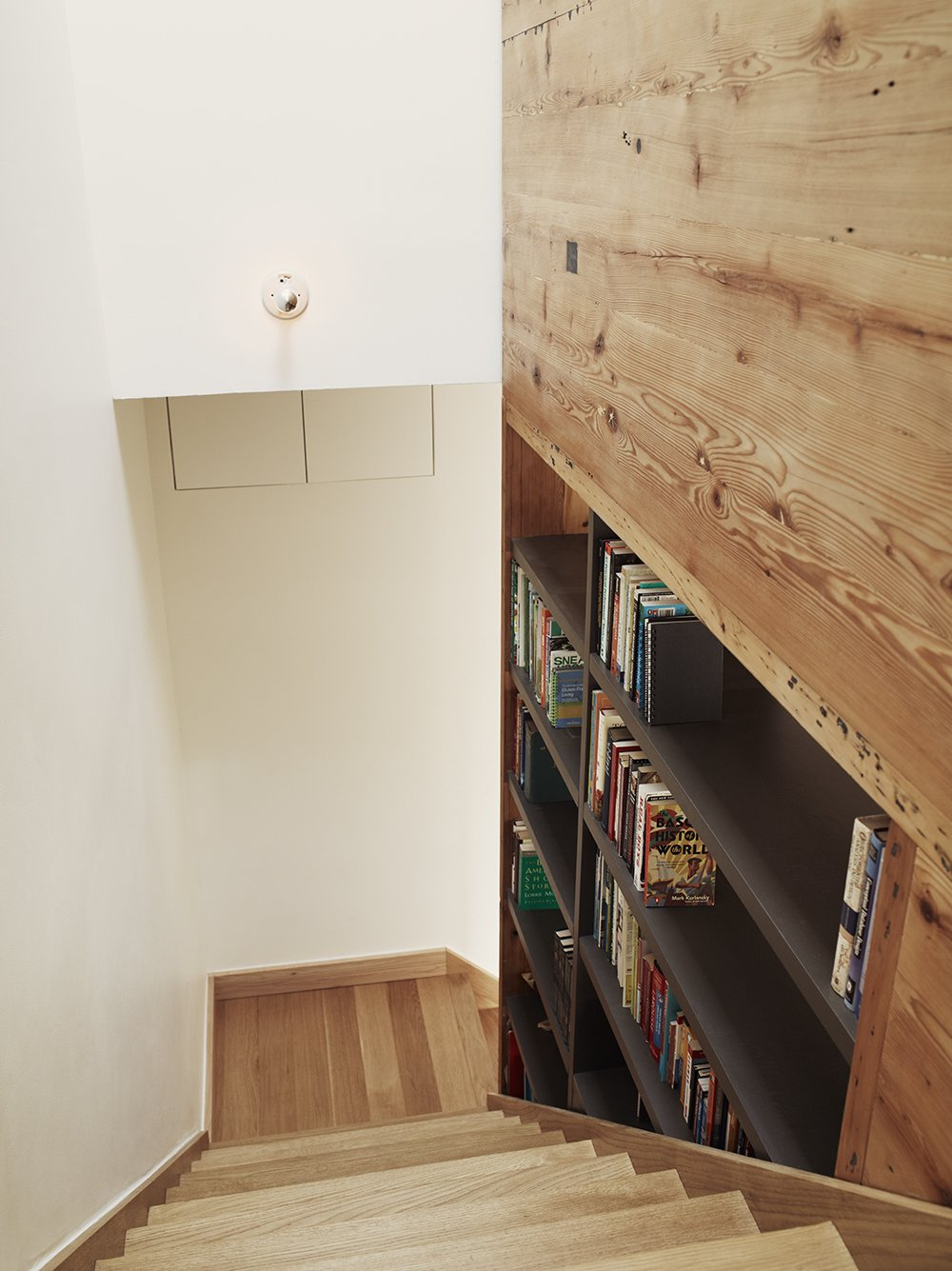 Creating a library along a staircase out of open shelving means that the books can be accessed from both the staircase and the stair hall on the other side.