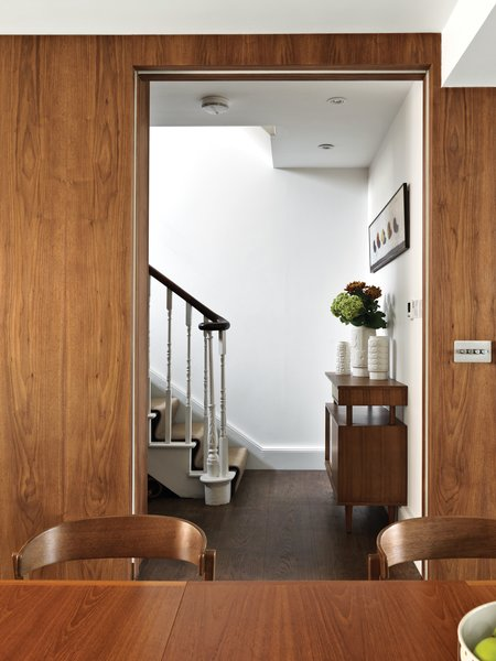 """Home of the Brave  In the ground-floor eating area, the design team wrapped the walls in rich walnut to instill warmth often found in mid-century homes. """"Sometimes one bold move is enough. Be brave with fewer statements,"""" Kiely advises. """"Go for the big thing rather than lots of little things."""" Kiely's Upholstered Dining Chairs from her House collection surround a Danish vintage dining table. Her Gloss vases adorn the hallway console, which is also from her House line.  Photo 5 of 5 in A Textile Designer's Home Is Unapologetically Colorful"""