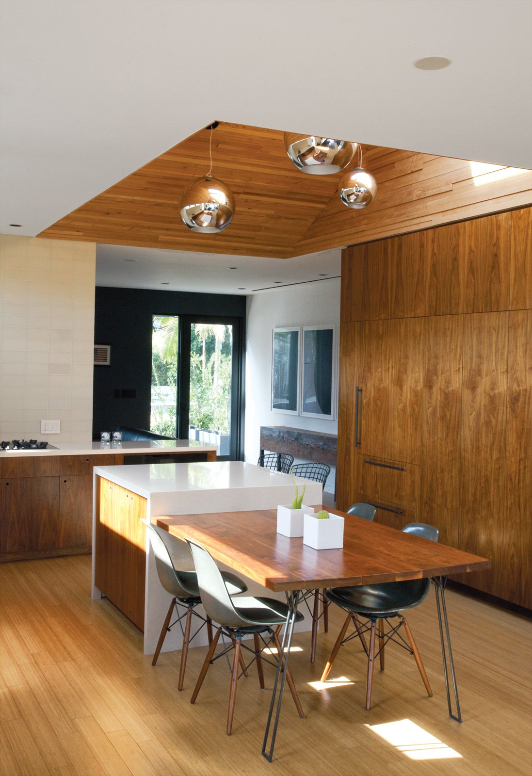 """Kitchen, Pendant Lighting, Wood Cabinet, and Cooktops Bill Thompson's Hollywood home exudes modern cool with a custom walnut dining table and chairs from Modernica.  Photo 1 of 9 in You Won't Be Calling This House a """"Man Cave"""""""