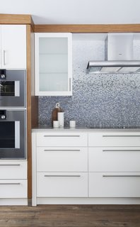 In Ontario, this 19th-century home abuts a river, where the residents enjoy kayaking and swimming in warmer months.  This geographic location partially inspired the wave-like backsplash. Each tile was hand-cut and individually placed by artisans from New Ravenna.