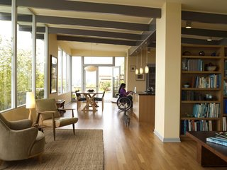 The main living area, which includes a more formal sitting area near the entrance, the dining area, Braitmayer's workspace and the kitchen, in which the couple's daughter works at the island. In the foreground is a pair of mid-century chairs; at left is a Heywood-Wakefield that Braitmayer found at an antiques shop. Seattle-based designer Lucy Johnson completed the interiors. The windows are from Lindal, and the exterior doors are from Marvin.