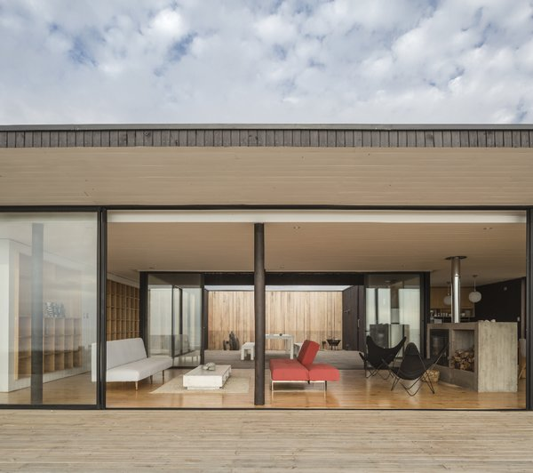 Aluminum lines the glass windows that divide the living spaces from the airy patio.