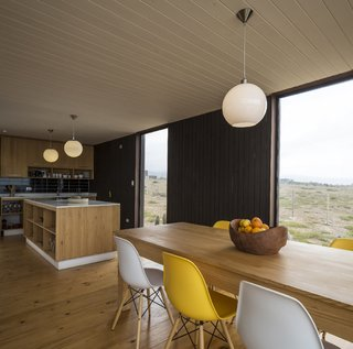 Eames DSW Molded Fiberglass chairs surround the dining table made of local wood and constructed by the owners.