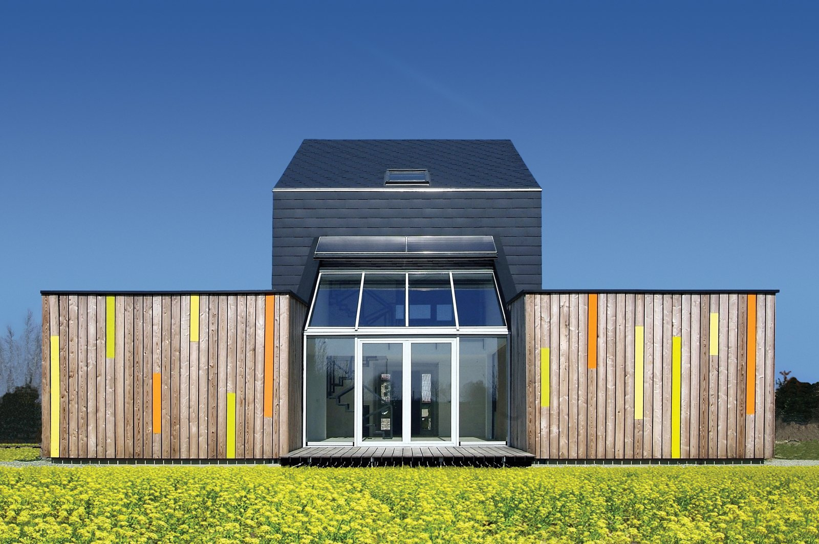 Exterior, Green Roof Material, and House Building Type The sun shines over the meadow on the backside of Kuczia's carbon-saving creation, whose central atrium contains the living room. In summer, the glass doors open.  Photo 1 of 3 in Modern Efficiency and Affordability Don't Have to Come at the Expense of Style