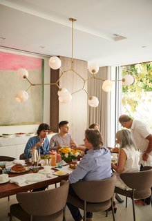 In the dining room, family and friends come together over a walnut-slab dining table from BDDW. The dining chairs are from Minotti, and the Branching Bubble chandelier is by Lindsey Adelman.
