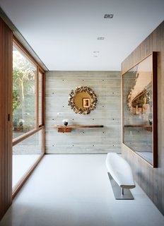 For the Highest Green Honor, One Couple Pulls Out All the Stops - Photo 8 of 12 - A Taryn Simon photograph in the entry greets visitors. The vintage Raindrops mirror is by Curtis Jere; the Lucellino table lamp is by Ingo Maurer.