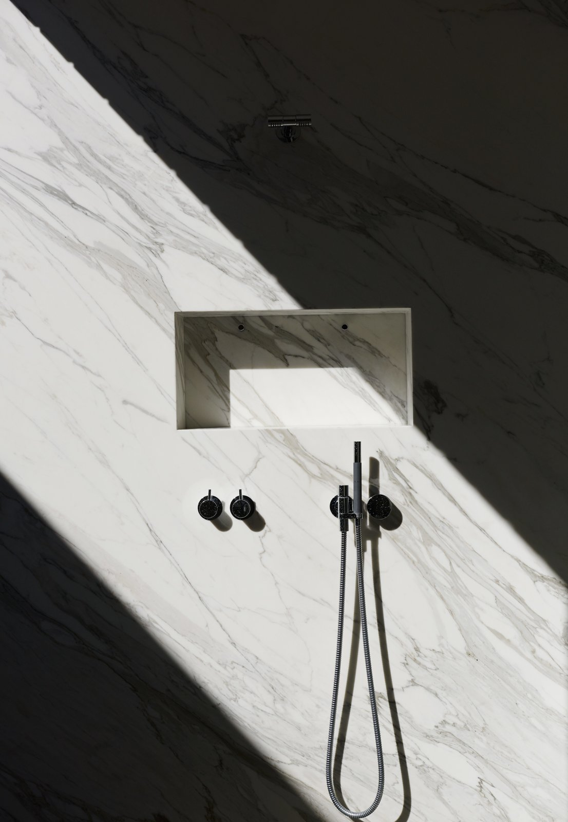 A shaft of sunlight streams into the marble shower, through a glass atrium that connects the master suite to the outdoors while maintaining privacy; the fixtures are by Vola. Tagged: Bath Room, Full Shower, and Marble Wall.  Photo 13 of 21 in Mad About Marble: 20 Kitchens and Bathrooms from For the Highest Green Honor, One Couple Pulls Out All the Stops