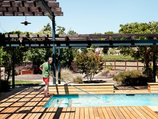 """A level, trellised garapa-wood deck connects the main structure to the pool house. """"The arbors near the pool knit everything together,"""" says Mikiten. """"The deck is constructed over a drainage pit so the wood surface can be completely flush with the interior floor and the surrounding yard, which is critical for a fluid experience by someone using a wheelchair."""""""