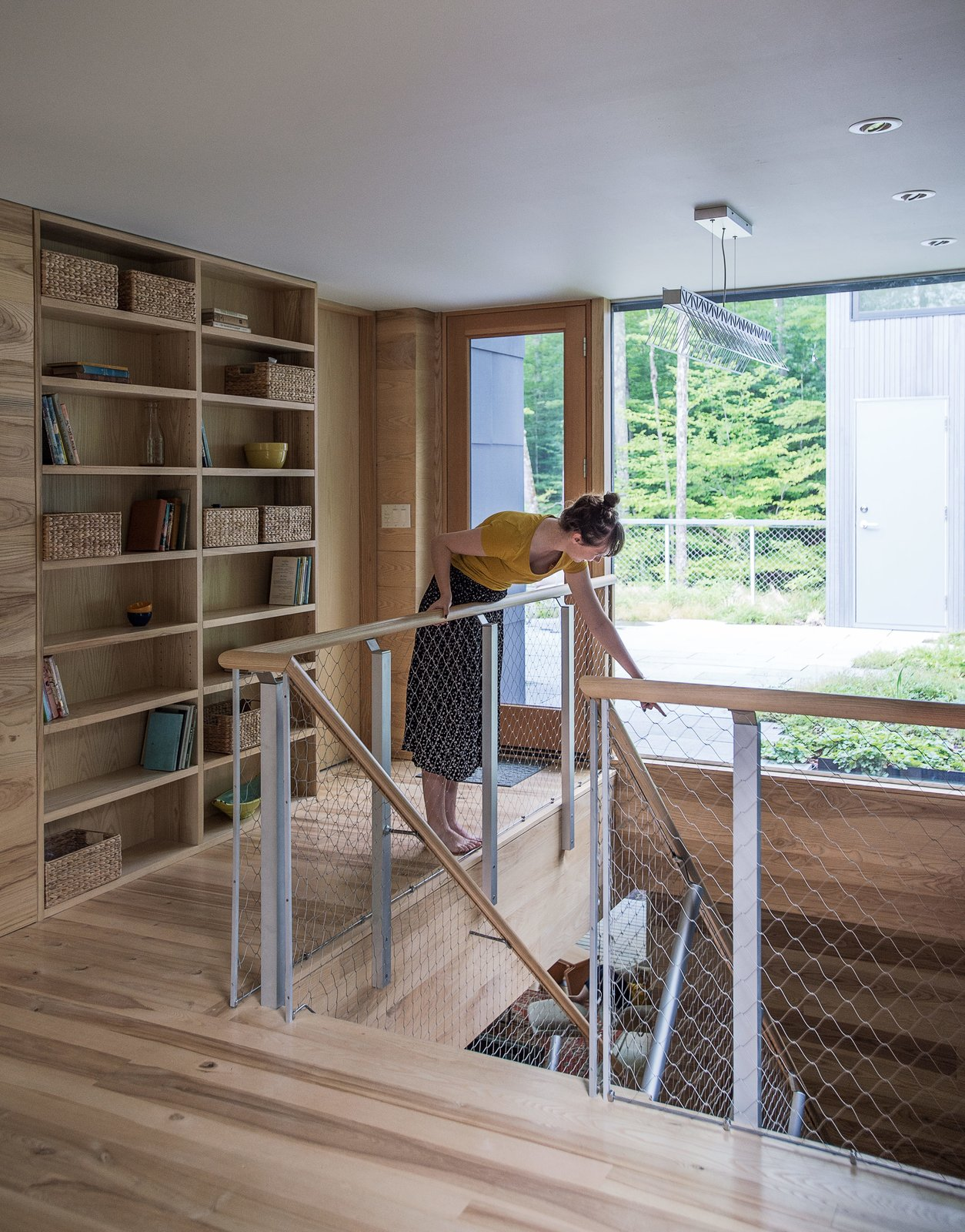Staircase, Metal Tread, and Wood Railing Beyond the second-floor landing, a garden roof filters rainwater and provides insulation.  Photo 4 of 13 in It Took a Whole Family to Build This House