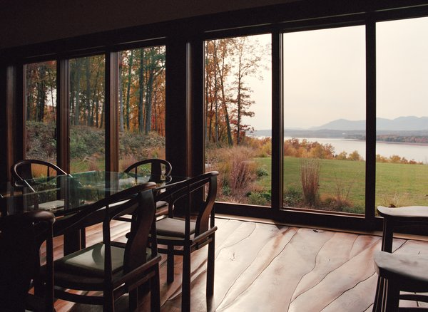 The sustainable home features handmade furniture and an undulating floor, all crafted from the site's felled black walnut trees. They lend a craft-oriented feel to the home that's otherwise strictly modern in design and detailing. The waves of the Hudson River are mimicked in the organic, wavy pattern of the walnut flooring.