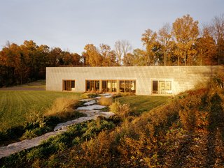When designing his own home, architect Allen Shope and his wife carefully designed an eco-friendly landscape that was inspired by river views and reclaimed elements, including granite slabs on the exterior and walnut flooring on the interior.