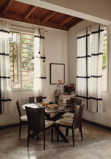 Adjacent to the kitchen, lit by an IKEA pendant light, is a dining area with a table and chairs purchased at a local Port-au-Prince store; the curtains are also from IKEA.
