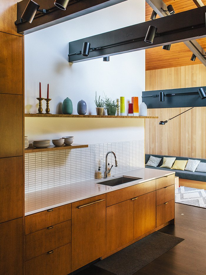 """Kitchen, Dark Hardwood Floor, Wood Cabinet, Undermount Sink, Track Lighting, Ceramic Tile Backsplashe, and Open Cabinet Helgerson selected white Savoy 1""""x4"""" stacked tiles from Ann Sacks for both the kitchen and bathroom.  Photo 3 of 5 in A Designer's Tips For Renovating a Midcentury Modern Interior"""