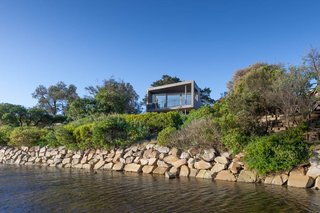 A small home in Australia is elevated to provide protection against potential flooding from the riverbank.