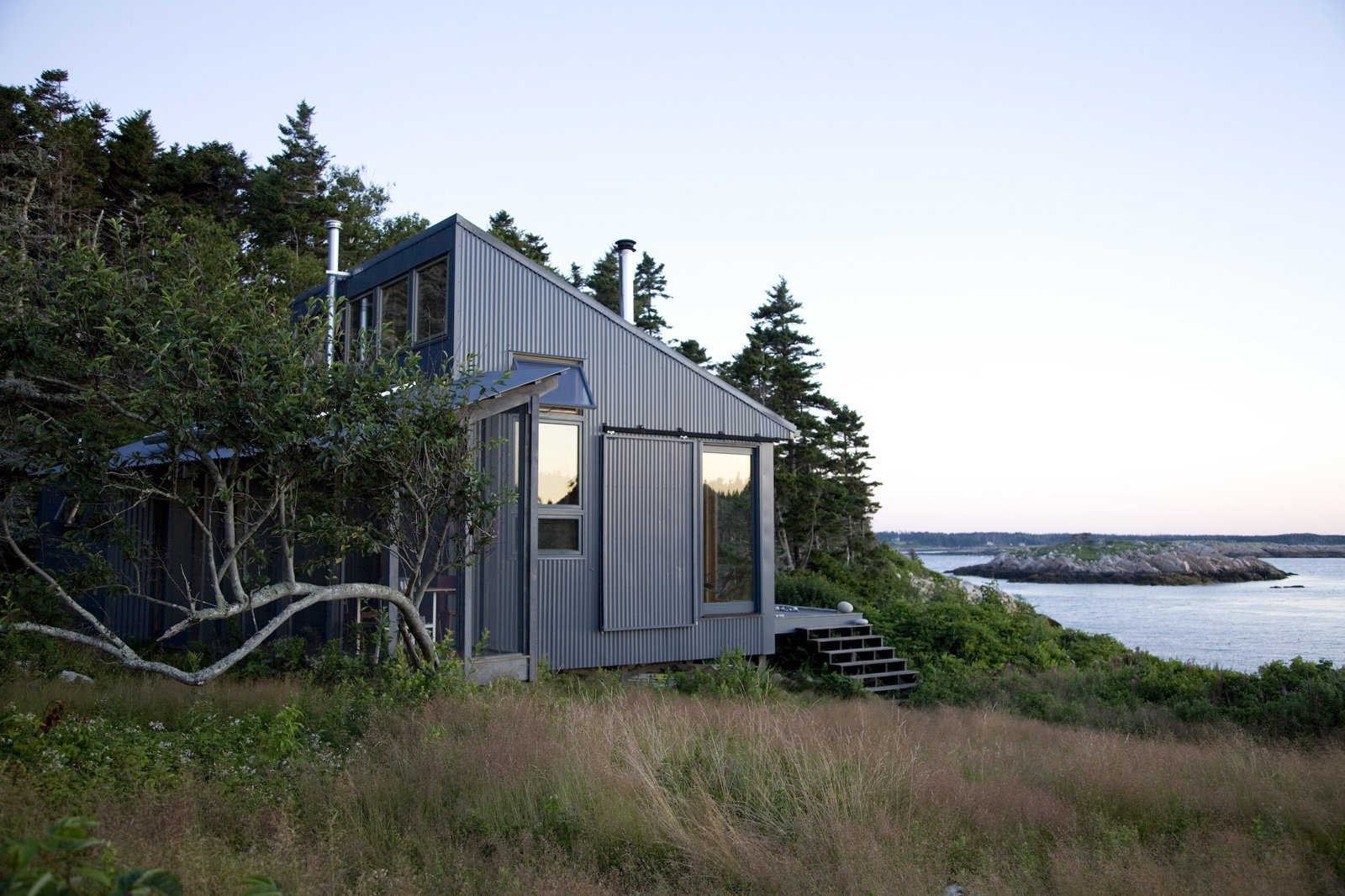 Exterior, House Building Type, Metal Siding Material, Cabin Building Type, and Shed RoofLine This quaint cabin is located on Ragged Island, 20 miles off the coast of Maine. Photo by: Eirik Johnson  Photo 73 of 101 in 101 Best Modern Cabins from Modern, Off-the-Grid Homes