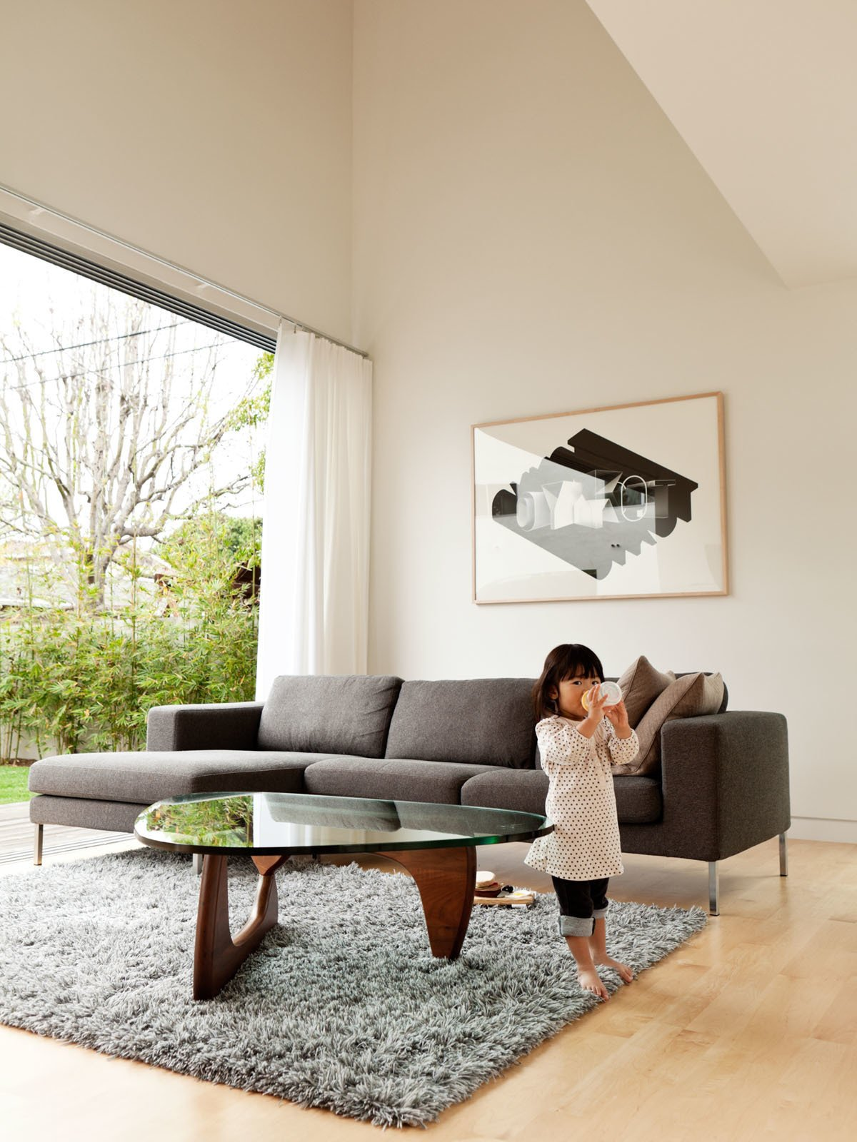 Living Room, Coffee Tables, Sofa, Light Hardwood Floor, and Rug Floor The living room is outfitted with the Stockholm Wool Rug from Ikea, a Noguchi table by Isamu Noguchi for Herman Miller, and the Neo Sectional Chaise Left by Niels Bendtsen from DWR.  Photo 8 of 13 in A Dream House for the Ages from Design Dictionary: Noguchi Table