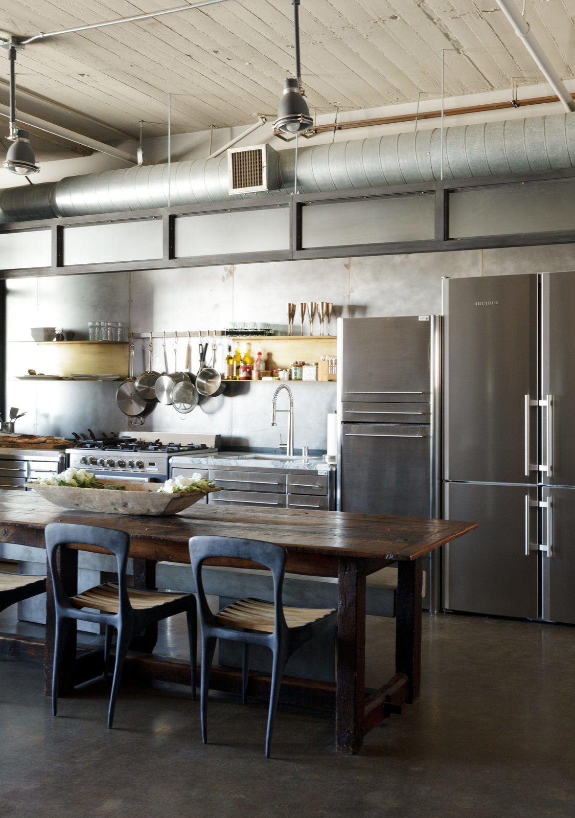 Kitchen, Refrigerator, Undermount Sink, Ceiling Lighting, Pendant Lighting, and Range In a loft renovated by designer Andrea Michaelson, a Liebherr refrigerator blends in with stainless-steel cabinets from Fagor. Flow chairs by Henry Hall Designs and CB2 benches pull up to an antique farm table.  Photo 2 of 6 in Steel and Brass Cover Nearly Every Surface of this Industrial L.A. Kitchen