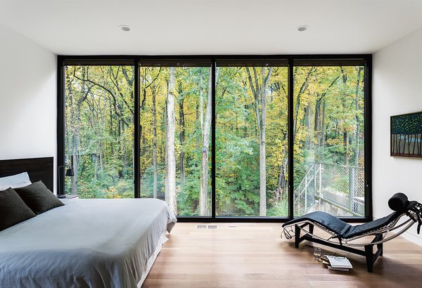 Floor-to-ceiling windows by Sunshine Glass feature a five-and-a-half-inch profile aluminum frame. The LC4 chaise in the master bedroom on the first floor is by Cassina.  Photo 5 of 11 in This Woodland Home in Virginia Was Built for Modern, Multigenerational Living