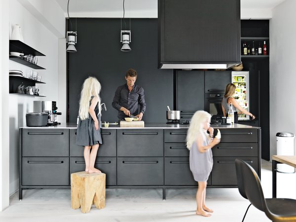 """Twin daughters Merle and Anine join their parents in the family's kitchen, designed by Jensen for Vipp. He explains that his role as chief designer at Vipp is to """"work with their DNA"""" by refining the company's trademark materials: stainless steel, painted metal, and rubber. For the utilitarian kitchen, """"we wanted to get the feeling of a tool,"""" he says. """"It's nice to have a space where you can actually work."""" The gas stovetop is by ABK and the refrigerator is by Smeg; Le Perroquet spotlights are from iGuzzini."""