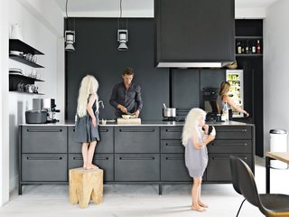 "Twin daughters Merle and Anine join their parents in the family's kitchen, designed by Jensen for Vipp. He explains that his role as chief designer at Vipp is to ""work with their DNA"" by refining the company's trademark materials: stainless steel, painted metal, and rubber. For the utilitarian kitchen, ""we wanted to get the feeling of a tool,"" he says. ""It's nice to have a space where you can actually work."" The gas stovetop is by ABK and the refrigerator is by Smeg; Le Perroquet spotlights are from iGuzzini."