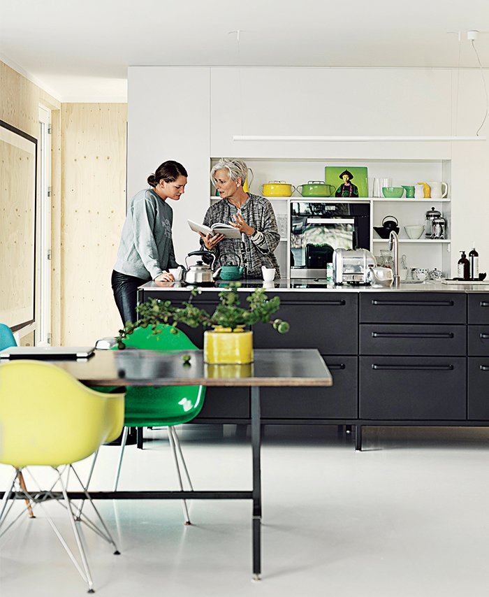 Kitchen and Open Cabinet The couple have crafted their own kitchens in the past. For their floating home, however, they selected the black Vipp kitchen, where Juul chats with her daughter, Karla.  Photo 5 of 9 in Each Day at This Floating Home Begins With a Swim, Just Two Feet From Bed