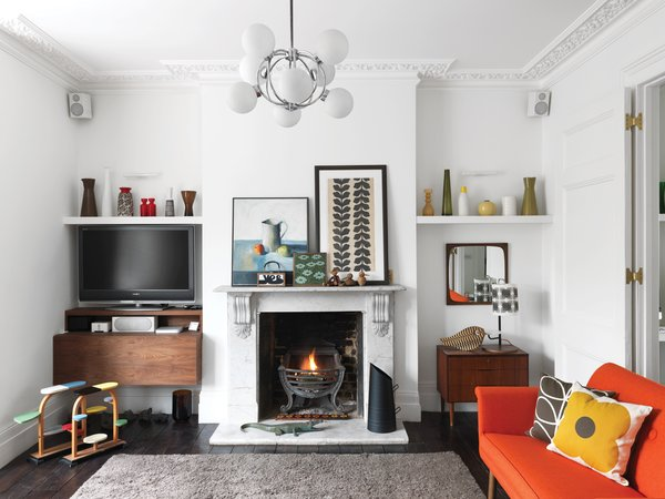 """Living Room, Dark Hardwood Floor, and Sofa Light My Fire  """"I didn't want to compromise the Victorian nature of the house,"""" she says. Although the original fireplace was in good shape, the flooring needed to be replaced. Kiely didn't want to use new wood, so she sourced the weathered ebony-colored boards from an architectural salvage yard. """"I wanted the floors to really feel like they were part of the house,"""" she says. Kiely found the rug at Heal's and the chandelier and art are vintage.  Photo 2 of 5 in A Textile Designer's Home Is Unapologetically Colorful"""
