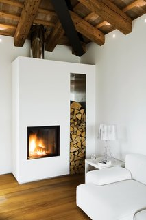 At a renovated farmhouse in the Italian countryside, a crisp, modern white plaster fireplace and hearth infuse the interior with coziness and warmth.