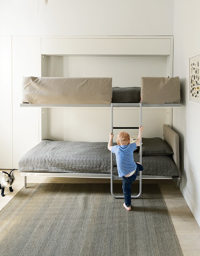 Kids Room, Bedroom Room Type, Playroom Room Type, and Boy Gender The bunk bed, the Lollipop IN model from Resource Furniture, stows away flush to the wall when not in use.  Photo 5 of 14 in How One Family of Three Does It All in 675 Square Feet from How to Take a Dwell Photo