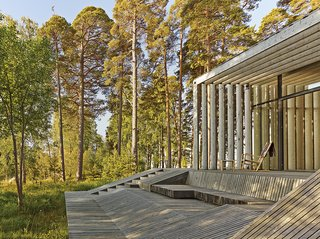 The wood on the exterior has been treated with linseed oil or painted with tar. Seats built directly into the pavilion's frame allow the family to relax and enjoy the surrounding woodlands without the need for additional furniture.