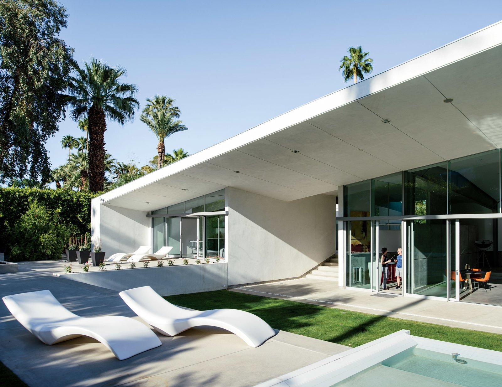 Outdoor, Large Pools, Tubs, Shower, Concrete Patio, Porch, Deck, and Grass Cloe chaise longues from Myyour surround the pool.  Photo 5 of 12 in An Energy-Efficient Hybrid Prefab Keeps Cool in the Palm Springs Desert
