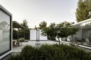 A Minimalist Mexican Retreat Uses an Array of Strategies to Beat the Heat - Photo 4 of 7 - One of the biggest challenges of the project was keeping the open courtyard cool enough for the residents to enjoy it. The architects used a low impact water feature to create ambient cooling and two native flamboyant trees to provide shade.