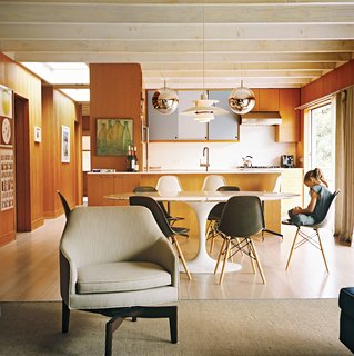 The open-plan living-kitchen-dining area is a repository of design icons, both classic and contemporary. There's a Louis Poulsen pendant lamp over the Eero Saarinen dining table; Mirror Ball pendants by Tom Dixon over the kitchen counter; and Tab F1 floor lamps from Flos behind the Edward Wormley–designed Dunbar sofa. In the living room, chairs modeled on Jens Risom's swivel design enable people to face either the sofa or to spin 180 degrees toward the kitchen.