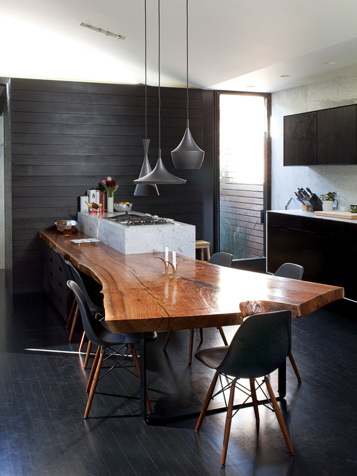 """Dining Room, Chair, Table, Dark Hardwood Floor, and Pendant Lighting The materials palette is similarly restrained, making the only natural piece of wood in the house—the almost 14-foot-long walnut slab in the kitchen—really stand out. """"If there was wood everywhere it would lose its gravitas,"""" notes Chris.  Photo 15 of 41 in 50 Dashing Dining Rooms from Designed In-House"""