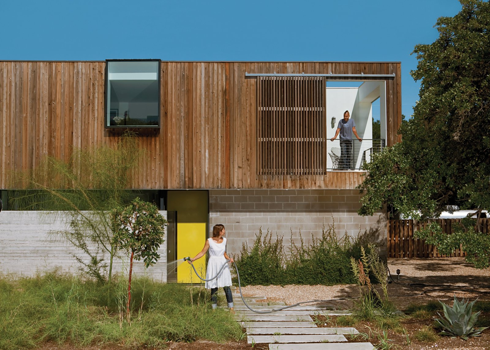 Exterior, House Building Type, Wood Siding Material, and Flat RoofLine Anne Suttles waters the bamboo muhly, palo verde, strawberry tree, and magic carpet thyme thriving in their Austin yard.  Photo 1 of 7 in A Green Home to Last a Lifetime in Austin