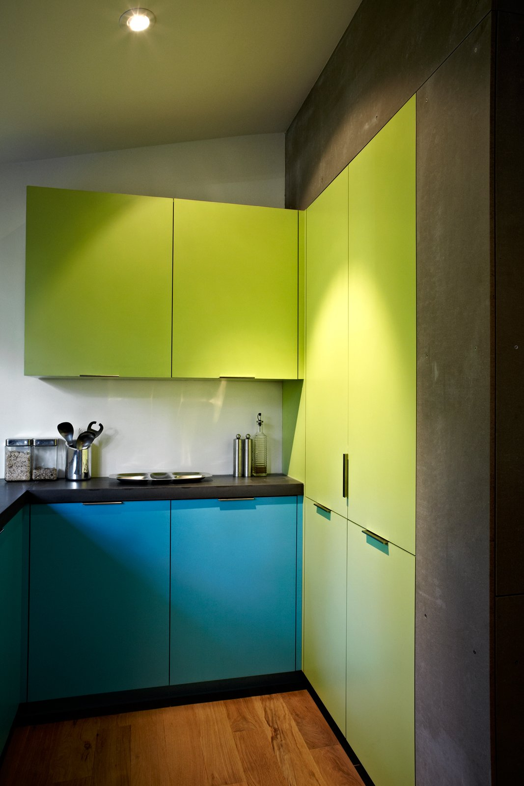 The eye-popping laminated cabinets are from Abet Laminati in Bloomberg's favorite colors. The gray walls are made from Viroc, a substance typically used to underlay other building materials. Photo by: Greg Powers  Photo 3 of 6 in Modern Kitchen Renovation with Mid-Century Roots