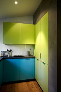 Modern Kitchen Renovation with Mid-Century Roots - Photo 3 of 6 - The eye-popping laminated cabinets are from Abet Laminati in Bloomberg's favorite colors. The gray walls are made from Viroc, a substance typically used to underlay other building materials. Photo by: Greg Powers