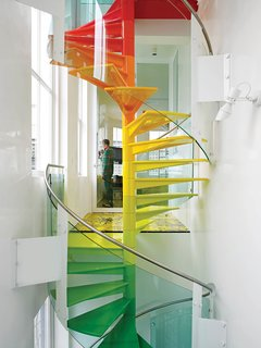 "A spiral staircase provides a prismatic path from floor to floor in this London home. ""The staircase is the hub, the soul of the project,"" designer Ab Rogers says. ""It's meant to be enjoyed."" From the ground, the steps start with the cool colors of the earth, then get warmer as they reach up to the sky."