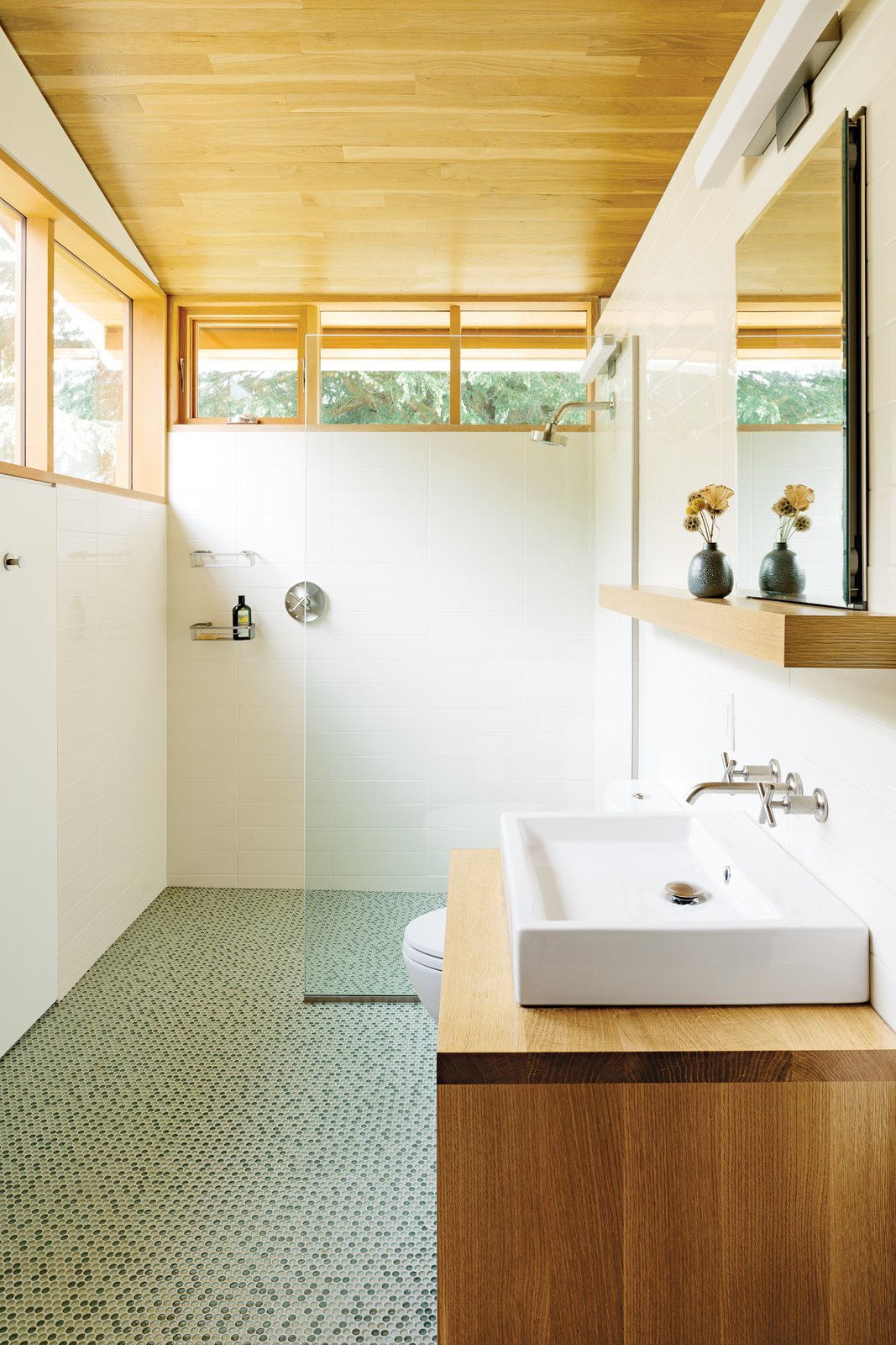 In the bathroom, a thin pane of glass separates the shower; an Aquaplane sink by Lacava hovers above   a built-in vanity illuminated by a lean Adelphi light by Oxygen Lighting; and blue-green glass penny tiles by Terra Verre decorate the floor. The absence of a door, combined with windows on two sides, makes the bathroom feel like a continuation of the overall space. Tagged: Bath Room, Vessel Sink, Full Shower, and Ceramic Tile Floor.  Photo 9 of 10 in Salvaged Wood Renovation in Portland