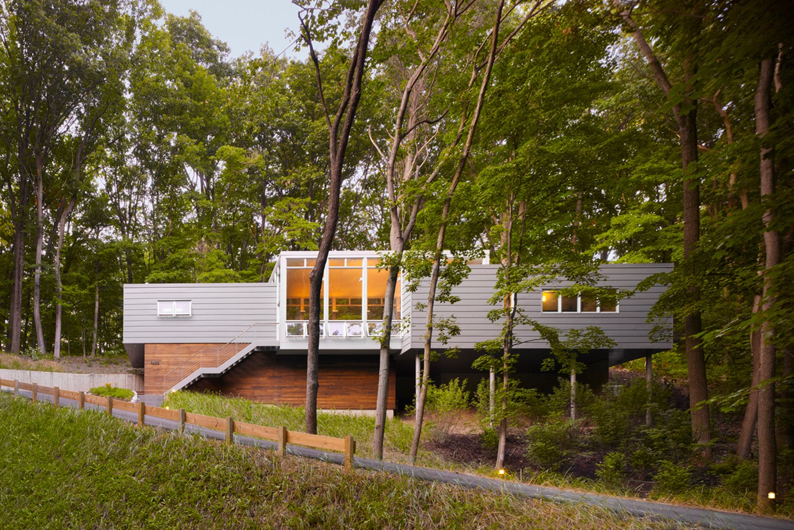 "Built on a challenging hillside site and tucked behind a thicket of trees, the Bridgman, Michigan, house designed by Scott Rappe provides a modern weekend retreat for a Chicago couple. ""One of my first responsibilities was getting the owners up to their house and essentially on one level. Because of the pie-shaped property, we needed to push the building up the hill to provide square footage for the program. By keeping the building perpendicular to the slope, using piloti on one side and a retaining wall on the dune side, we were able to insert foundations with minimal disturbance,"" says Rappe.  Photo 6 of 20 in 20 Modern Homes From the Midwest from Michigan Modern: 7 Homes in the Great Lake State"