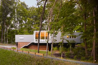 "Built on a challenging hillside site and tucked behind a thicket of trees, the Bridgman, Michigan, house designed by Scott Rappe provides a modern weekend retreat for a Chicago couple. ""One of my first responsibilities was getting the owners up to their house and essentially on one level. Because of the pie-shaped property, we needed to push the building up the hill to provide square footage for the program. By keeping the building perpendicular to the slope, using piloti on one side and a retaining wall on the dune side, we were able to insert foundations with minimal disturbance,"" says Rappe."
